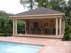 This impressive outdoor cooking area features a hip roof for 50000 pool design