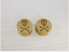 "Double Flared ""Saddle Plugs"" with a Skull & Bones design engraved.  Available in various sizes ranging from 1/2"" (12mm) to 11/16"" (20mm). Saddle Plugs are made from wood. 1 pair includes 2 plugs."