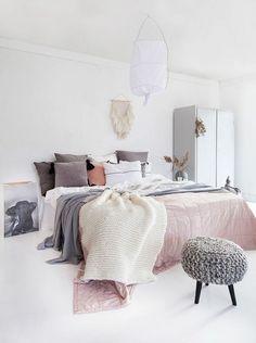 cama con ropa de cama revuelta, cojines en fila, mantas y plaids