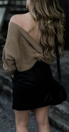 Edgy winter outfit styled with oversized tan sweater, leather mini skit, and snakeskin booties
