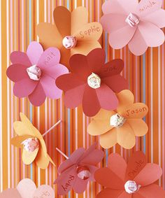 Paper flowers made from heart shapes with a sucker center.