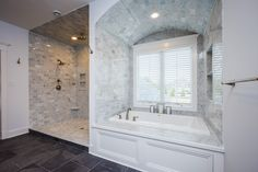 Dream Master Bathroom with custom tile work.  Kohler soaking tub surrounded by beautiful grey tile to the ceiling.