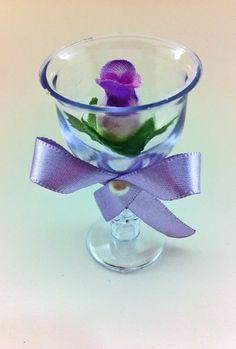 Tacinha em acrílico, com flores ou rosa artificial nas cores escolhidas pelo cliente. <br>Laço a escolher, com fita na cor desejada. <br> <br>Altura: 7.00 cm <br>Largura: 3 cm <br>Comprimento: 3 cm <br>Peso: 10 g