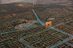 Algeria. Timgad, called Thamugas by the Romans, was a Roman colonial town in North Africa founded by the Emperor Trajan around 100 AD. The ruins are noteworthy for being one of the best extant examples of the grid plan as used in Roman city planning.