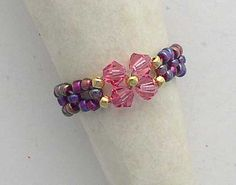Rose Swarovski crystals are accented with 22 KT gold seed beads. The band is woven with amethyst/pink seed beads.