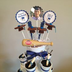 Graduation dessert.  Dessert Tower topper I made & designed filled with graduation cap pops (Reese's, Ghiradelli squares, a blue m & m, and a raspberry sour ribbon), rock candy, and a few items personalized for the graduate.
