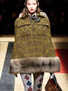 Für alle, die englische Eleganz mehr schätzen als Funktionalität, vereint Prada hier zwei große Wintertrends miteinander:Capes und Karo-Muster. In der Kombi erinnert der Look ein wenig an Sherlock Holmes. Wem das zu viel Detektiv-Feeling ist, kann die Trends auch unabhängig voneinander tragen.