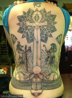 Steph's Egyptian back tattoo features geometric dotwork patterns, Anubis, Horus, Eye of Rah, an obelisk, an ankh and lilies.