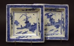 A Pair of Square Transitional Porcelain Dishes Made For the Japanese market. Decorated in Blue and White With a Central Watery Landscape With a Figure on a Spit of Land Watching Boats (Three on one dish and two on the other). The Border is Painted With a Scrolling Design in Blue Over a Paler blue. Both Dishes Have The Firing Faults That Were Required By The Japanese Market.