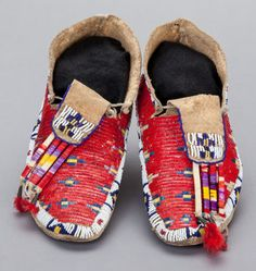 A PAIR OF SIOUX BEADED AND QUILLED HIDE MOCCASINS.
