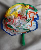 Mother's Day flower craft - decorate 5 round coffee filters, stack and pinch together the ends, fold 5in green pipe cleaner in half, put pinched end of filters between open ends and tape to secure, fold out filters to open flowers