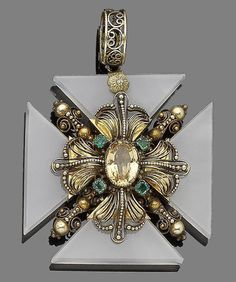 A topaz, emerald and chalcedony revival Maltese cross pendant, circa 1830.  The chalcedony cross, centrally-set with a foiled oval-cut topaz in a closed-back setting, within a cannetille surround highlighted with similarly-set square-cut emeralds, suspended from a pierced loop, length 6.0cm