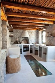 Masonry kitchens with built-in stone or cement shelves and cement sinks. THis one has open shelves. Besides the fantastic glass floor, of course!