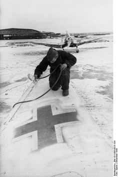 German aircraft getting white paint for the winter camuglagem, Western Europe, Dec 1943; Note in the background is the Ju 87 Stuka Dive Bomber