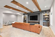 This cozy dark wood basement is the perfect place to curl up for the winter. Ready for entertaining at the holidays, this basement includes a custom built wet bar, home theater, home office, and game room. Start your custom basement remodel today with FBC Remodel in Colorado, Minnesota, and Illinois. Finished Basement Company, Living Area, Living Spaces, Basement Inspiration, Entertainment Room, Basement Remodeling, Remodels, Bars For Home, Home Theater