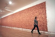 Richard Long: A woman walks past a Richard Long mud painting in the Tate Britain
