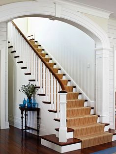 A wide arch, framed with substantial moldings and columns, provides an elegant introduction to the staircase.