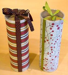 Pringle Cans decorated with wrapping paper and ribbon - perfect container for cookies!  I am so doing this!