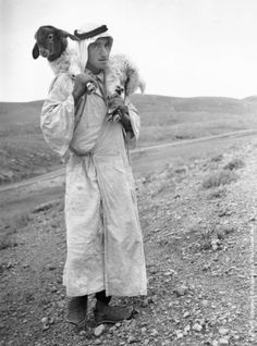 1938: A Bedouin shepherd carrying a young lamb on the hills of Palestine
