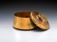 Achaemenid Gold Bowl with Lid  Gold, 6th-5th century B.C.E. D. 10 cm.  This bowl has a flat base and its cylindrical form is slightly puckered at the top. The bowl has a lid with a central, hammered, disk-shaped protruding handle.  Text and image from the website of the Miho Museum.