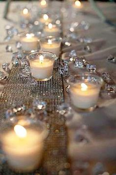 White table cloths with gold runner and tealights and diamond or gold glitter candle scatters.  Pretty and simple and inexpensive.