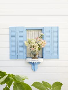 thrift store ledge painted to match the home's cheery blue trim stands in for a window box below this 13-inch-wide window.