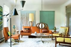 The combination of flokati shag carpeting, three armed swing lamp and plywood hanging chandelier really add details to this mid century modern living area.