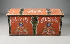 Liten rosemalt kiste med rød bunnfarge og datering 1886. L: 100 cm. Prisantydning: ( 1500 - 2000)