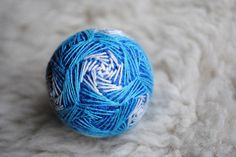 This listing is a for a blue temari ball in a wave design, a decorative gift for any home and a thoughtful present for those you love.  This hand-made, embroidered ball based on an ancient Japanese craft, is made with recycled materials, including polyfill, acrylic yarn and nylon and cotton threads. Symbolizing good luck and all the best wishes for you from the maker, it is the perfect decoration or gift for a loved one. Over a core of plastic and polyfill, innumerable wraps of acrylic yarn…