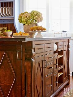 This wood island features decorative details that add easy elegance. The piece is pretty and practical. Drawers, cabinets, and open-air shelving ensure that the piece will hold everything, inculding bread and potatoes. A black granite countertop hides smudges.