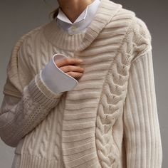 A fitted sweater formed from cashmere, cotton and wool blends of varying weights and patterns for textural dimension. The ribbed neckline extends into a sculptural drape at the shoulder in homage to Henry Moore's work.