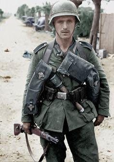 A German infantryman standing in a street.