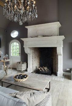 Bourgondisch Kruis Designs | Grand fireplace, greige décor and stunning chandelier