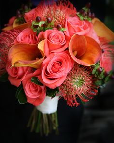 Beautifully textured fall wedding bouquet. Designed with orange pincushion protea, mango calla lilies, coral roses, and burgundy hypericum berries. By Backyard Garden Florist.