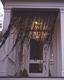 Create a spooky entrance by cutting up black trash bags into thin pieces. You can use a tension rod (used for hanging drapery) for the base. Or use your shower rod and attach the bag around the rod to create a curtain effect. Make sure the strips are uneven and long. Gather some brooms to lean around the door and use a softer porch light.