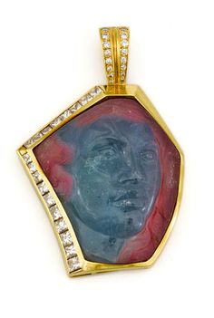 A carved tourmaline cameo and diamond pendant/enhancer carved multi-color tourmaline cameo measuring approximately: 40.0 x 35.2 x 11.4mm; estimated total diamond weight: 2.75 carats; mounted in eighteen karat gold; length: 2 3/8i