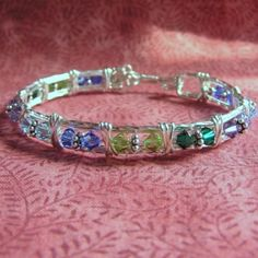 This is a wire wrapped bracelet I made which birthstone colors for a customer. This bracelet can be created with any color Swarovski  crystals or genuine gemstones.
