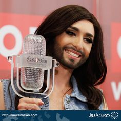 """Austria's Conchita Wurst poses with her trophy after a news conference in Vienna May 11, 2014. Wurst, popularly known as """"the bearded lady,"""" won the 59th annual Eurovision Song Contest"""