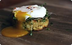 poached egg on quinoa cake w/ broccoli spouts.