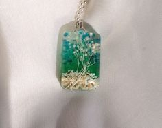 I created this one of a kind landscape resin pendant with a bit of dried flower, a mix of sand and peach glass granules, bits of green feather and a