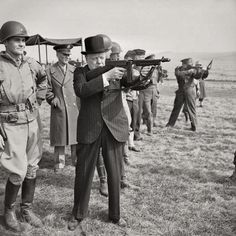 Winston Churchill fires a Thompson submachine gun alongside the Allied Supreme Commander, General Dwight D Eisenhower, during an inspection of US invasion forces, March 1944