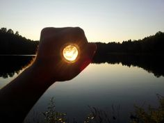 I caught the sun in my hand! Nice effect of capturing the sun with a bottle on the shore of a lake in Sweden