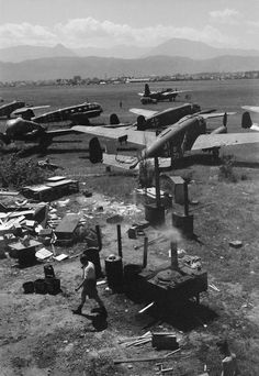Cooks of No. 324 Wing RAF, Desert Air Force, prepare the midday meal in field ovens set up by the airfield at Klagenfurt, Austria. Parked in the foreground are a number of Siebel Si 204 communications aircraft left by the Germans and, beyond them, a Douglas Boston of No. 232 Wing RAF.