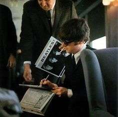 John Lennon signs Beatle album covers.