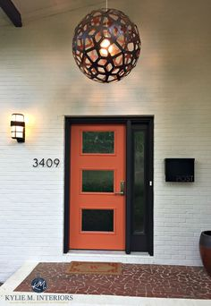 Exterior front door mid century style painted orange with dark brown black trim and painted brick in a cream beige tone. Kylie M Interiors E-design and ONline Colour consulting decorating expert - July 20 2019 at Orange Front Doors, Best Front Doors, Black Front Doors, Modern Front Door, Exterior Front Doors, Black Door, Black Exterior, Front Entry, Front Door Paint Colors