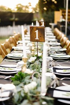Gray tablecloth, eucalyptus table garland, white candlesticks, and wood table number | Image by Richard Cao