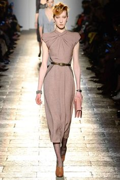 Nougat coloured midi length dress with a forties inspired draped neckline, a accentuate waist with a narrow metallic belt and a natural flowing skirt below the knee. Dark transparent pantyhose in brown leather pumps with the high cut. The hairdo give a clear nod to the 40s. Look by Bottega Veneta Autumn/Winter 2017 Ready-to-wear Collection