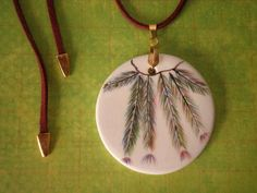 Mandala de cerâmica pintada à mão, esmaltada e queimada.  Colar com aprox. 48 cm de comprimento.  Mandala: 5 x 5 cm de diâmetro  O fio é de couro ecológio (camurça) na cor marrom, com finalizadores dourado.  A peça é fixada com jacaré dourado.  O tamanho pode ser ajustado.    Faça já sua encomend...