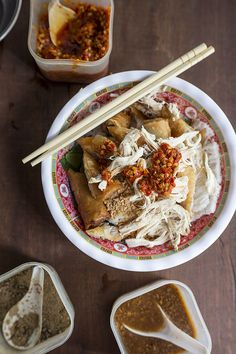 utensils included - Cambodia Street Food - Eating Asia in Siem Reap: Rice vermicelli topped with crispy chicken-filled spring rolls and shredded chicken meat, served with pickle and chili sauce.