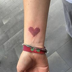 Cross stitch style red heart tattoo on the right inner wrist.